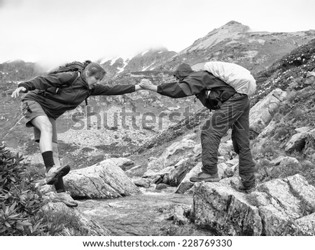 Monochrome image of a young man with a backpack helps frightened woman to overcome the creek on the background of snowy mountains - stock photo
