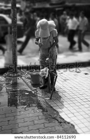 Monochrome image of an unidentified old woman tapping water from a public water pipe on the busy street of Kuala Lumpur's Chinatown.