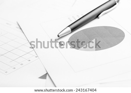 Monochrome image of ballpoint pen lying on a business document with pie graph, focus to the text Sale. - stock photo