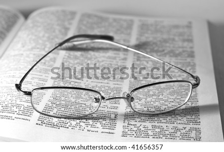 Monochrome image of glasses on an open book