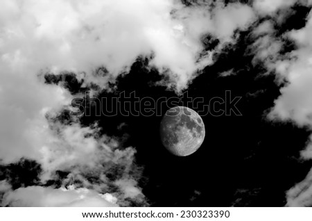 Monochrome image of moon and clouds at night - stock photo