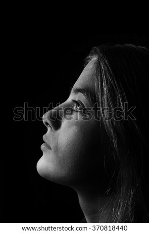 Monochrome low-key portrait of young beautiful girl. Black and white teenager portrait. - stock photo