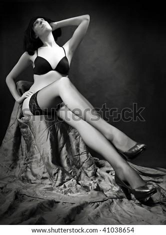 Monochrome low key studio shot young beautiful women dressed in black lingerie. - stock photo