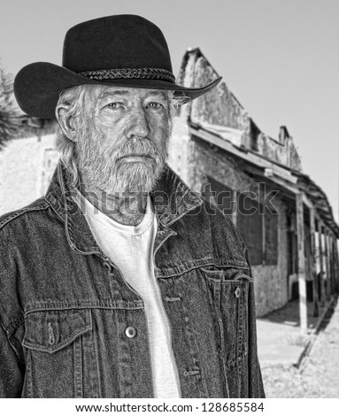 Monochrome of a tough old cowboy with a ghost town in the background - stock photo