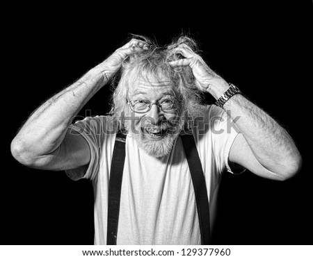 Monochrome of Senior with a crazed look on his face and hands grabbing his hair isolated on black - stock photo
