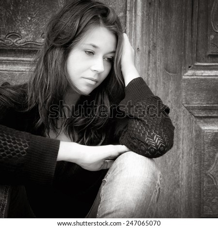 Monochrome outdoor portrait of a sad teenage girl looking thoughtful about troubles - stock photo