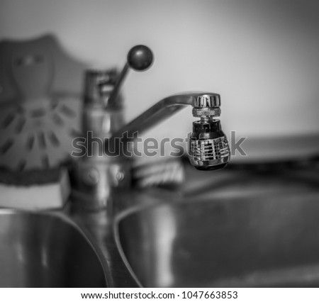 Monochrome photo of kitchen water tap with short depth of field and smooth out of focus bokeh.