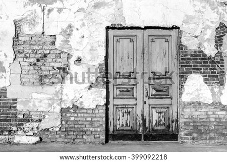 Monochrome photo of old textured brick wall and door. Bright sunlight. - stock photo