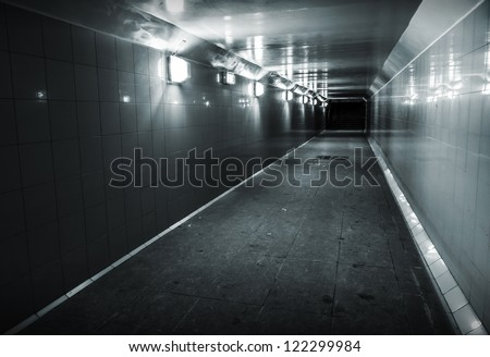 Monochrome photo of underground passage with lights and stairs in dark end