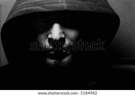 Monochrome picture of a guy in a hood - stock photo