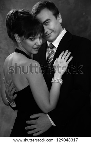 Monochrome picture of young man and woman in elegant evening dress