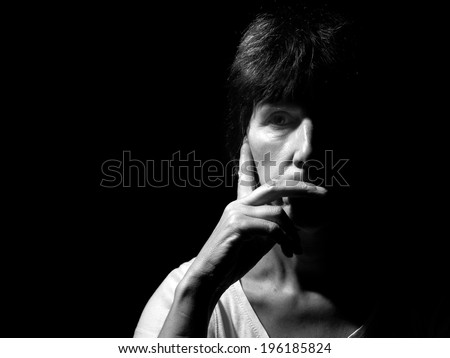 Monochrome portrait, face of a middle aged woman. Pensive, thoughtful. Rembrandt style lighting. - stock photo