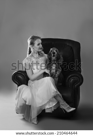 Monochrome portrait in black and white of beautiful blonde woman on leather couch with spaniel dog on her lap - stock photo