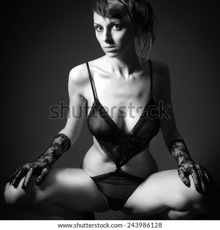 Monochrome portrait of a beautiful woman in sexy lingerie in front of black studio background - stock photo