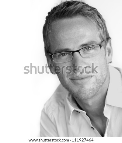 Monochrome portrait of a good looking young businessman in stylish eyeglasses - stock photo