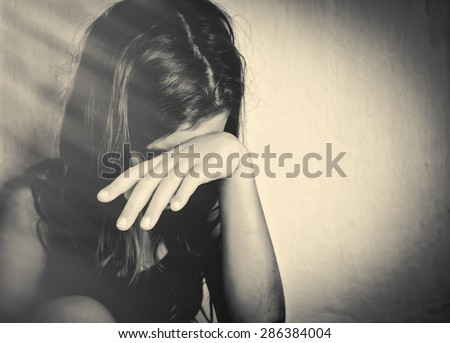 Monochrome portrait of a sad and lonely girl crying with a hand covering her face (with space for text) - stock photo