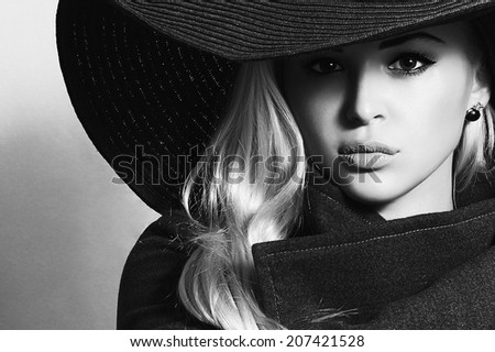 Monochrome portrait of Beautiful Blond Woman in Black Hat. Fashionable Lady in Topcoat. Elegance Beauty Girl - stock photo