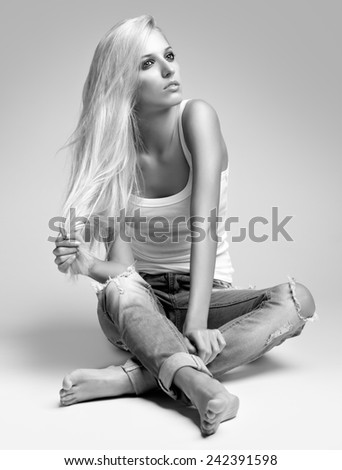 Monochrome portrait of blonde young woman in ragged jeans and vest sitting on floor on gray background - stock photo