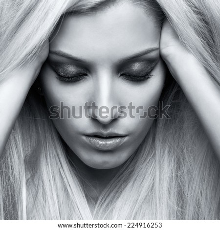 Monochrome portrait of blonde young woman on gray background