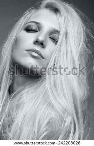 Monochrome portrait of blonde young woman on gray background - stock photo