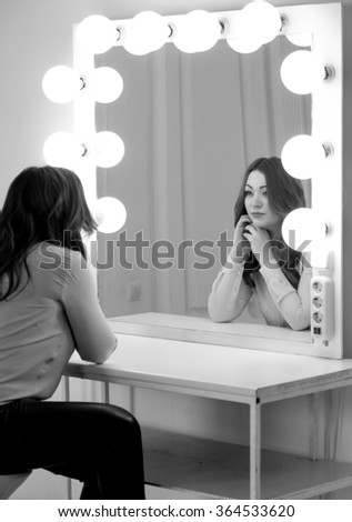 Monochrome portrait of elegant brunette woman looking at reflection in mirror with light bulbs - stock photo