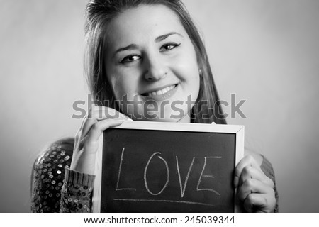 """Monochrome portrait of smiling woman posing with blackboard with word """"Love"""" - stock photo"""