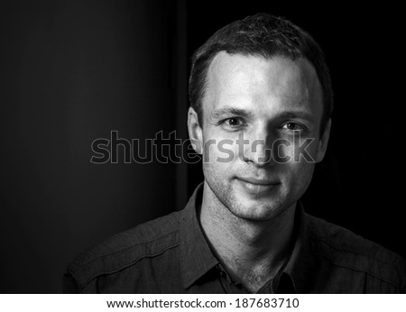 Monochrome portrait of young smiling Caucasian man on black background - stock photo