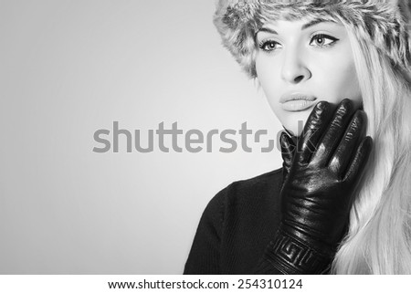 Monochrome portrait of Young Woman in Fur Hat. Beautiful Blond Girl in Black Leather Gloves. Winter Fashion Beauty.Your text here