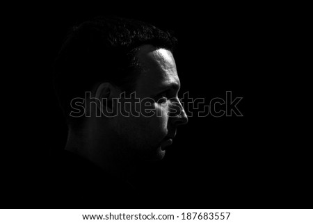 Monochrome profile portrait of young Caucasian man on black background