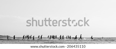 Monochrome sea landscape; crowd of people racing one another running into the sea - stock photo