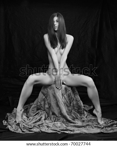 Monochrome shot of a naked beautiful woman posing on a black background.