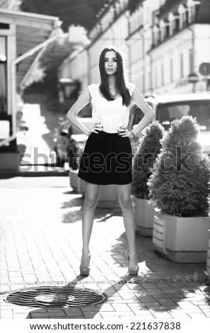 Monochrome shot of sexy slim woman in classic clothes standing on street