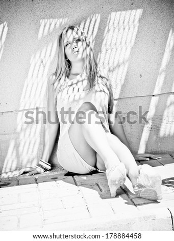 Monochrome shot of sexy woman leaning against wall at sunny day