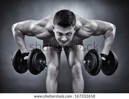 Monochrome shot of young athletic man working with heavy dumbbells - stock photo