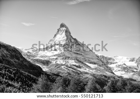 Monochrome view on snowy Matterhorn, other mountains and pine trees, Switzerland