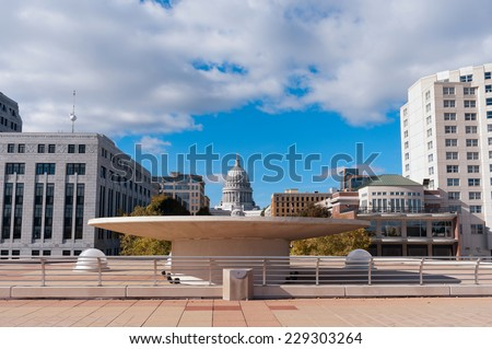 Monona Terrace with fountain in the foreground and the state capitol building in the distance in downtown Madison Wisconsin - stock photo