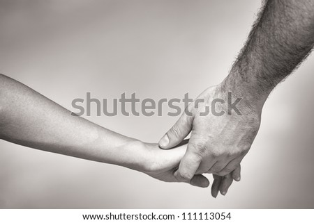 monotone shot of couple holding hands - stock photo