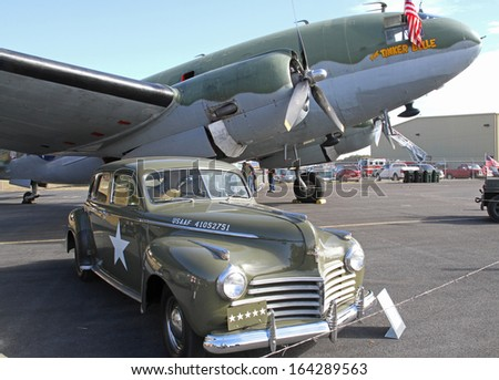 MONROE, NC - NOVEMBER 10:  Curtiss-Wright C-46  Commando Aircraft and 1941 Chrysler staff car on display at the Warbirds Over Monroe Air Show in Monroe, NC, on November 10, 2013.