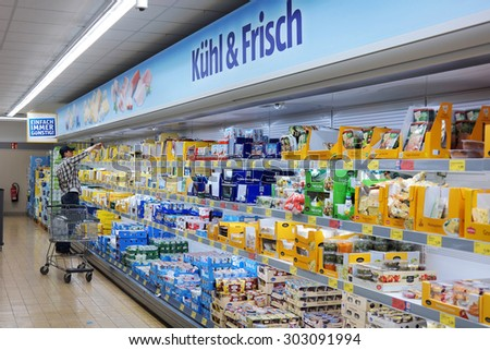 MONSCHAU, GERMANY - JULY 25: Man with a trolley shopping in the refrigerated fresh products aisle of an Aldi supermarket. Aldi is a global discount supermarket chain. Taken on July 25, 2015 in Germany - stock photo