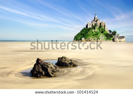 Mont Saint Michel with boulders in the foreground. - stock photo