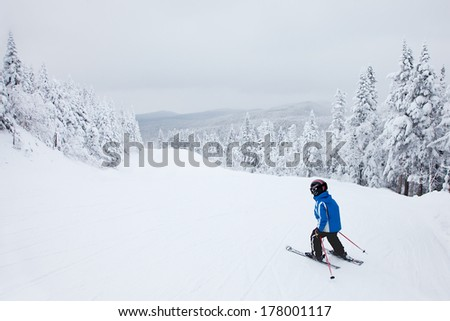 MONT-TREMBLANT, QC, CANADA -FEBRUARY 9: A boy is skiing down an easy slope at Mont-Tremblant Ski Resort on February 9, 2014. It is the best ski resort in Eastern North America.