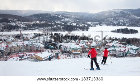 MONT-TREMBLANT, QC, CANADA -FEBRUARY 9: Skiers and snowboarders are sliding down the main slope at Mont-Tremblant Ski Resort on February 9, 2014. It is the best ski resort in Eastern North America.