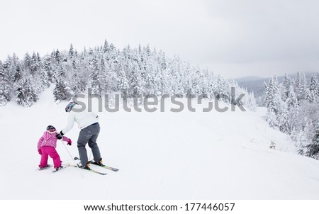 MONT-TREMBLANT, QUEBEC, CANADA - FEBRUARY 9:  A mother is teaching her young daughter to ski down an easy slope at Mont-Tremblant on February 9, 2014, the best ski resort in Eastern North America.