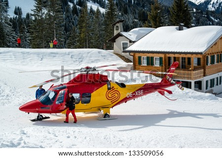 MONTAFON, AUSTRIA - MARCH 16, 2013: A rescue helicopter ready to evacuate a skier after a heavy accident in Montafon, Austria. Skiing safety is becoming more and more of an issue due to crowded slopes