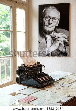 MONTAGNOLA, SWITZERLAND - AUGUST 28, 2012: portrait and original typewriter in Hermann Hesse museum in Montagnola, where famous poet and writer 1931-1962 lived. August 28, 2012 Montagnola, Switzerland