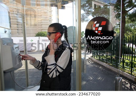 MONTE CARLO, MONACO - OCTOBER 29, 2014: A young woman uses an outdoor pay telephone owned and operated by state telecommunications carrier Monaco Telecom International (MTI) - stock photo