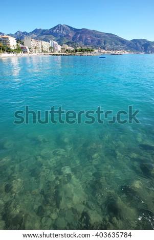 Monte Carlo, Monaco - September 20, 2015: view from far shore at resort city by blue sea coastline beach on mountain scene - stock photo