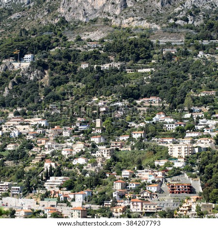 Monte Carlo, Monaco - September 20, 2015: view of mountain with densely populated city with residential buildings green trees on cityscape background, square picture