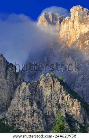 Monte Cristallo with tall summits surrounded by clouds as seen from passo Tre Croci, Dolomite Alps, Italy - stock photo