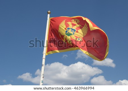 Montenegro flag in pole on blue sky background